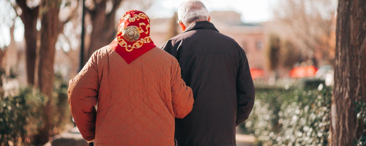 an elderly couple walking arm in arm