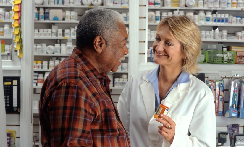 Pharmacist helping man with his medication