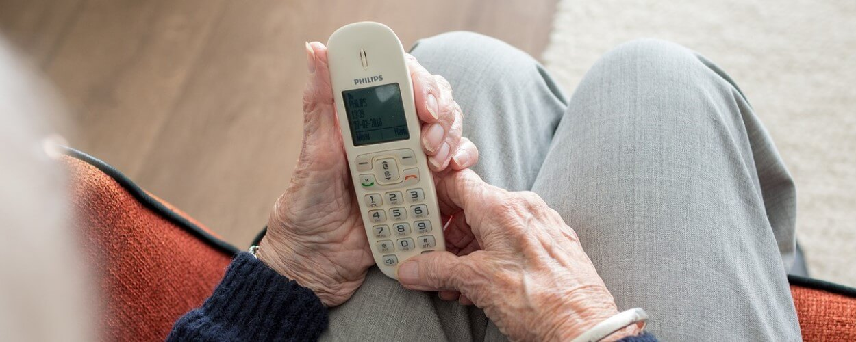 Elderly Person Holding Telephone