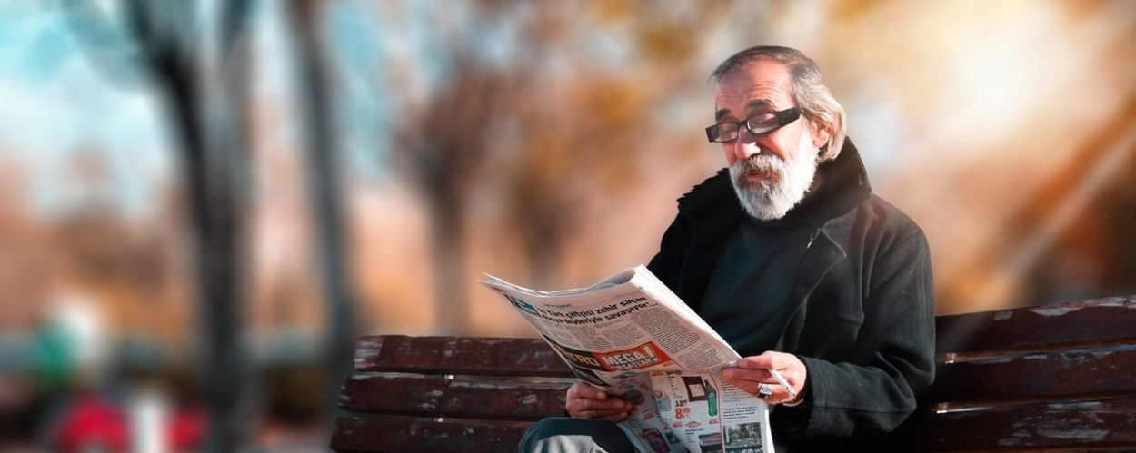 Elderly Man Reading Newspaper on Bench