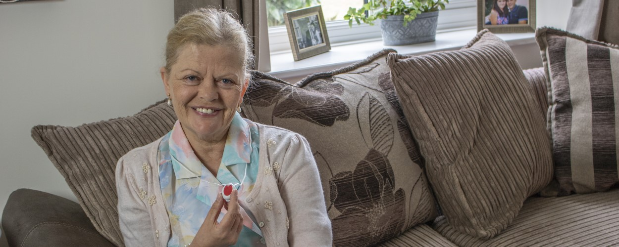 Older woman holding personal alarm device