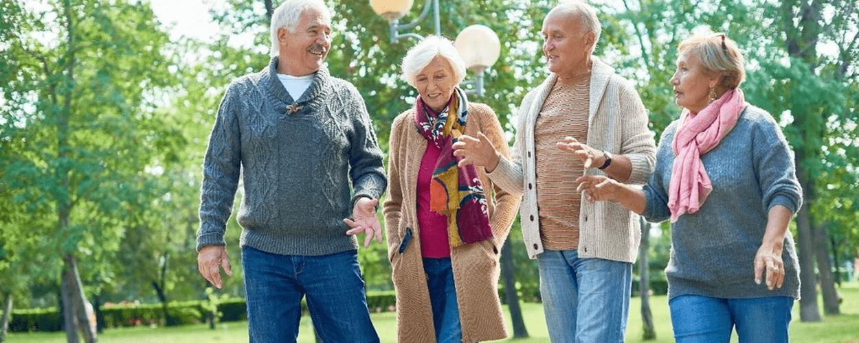 Four older people walking outside