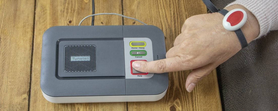 Careline alarm user pressing the red button on the base unit