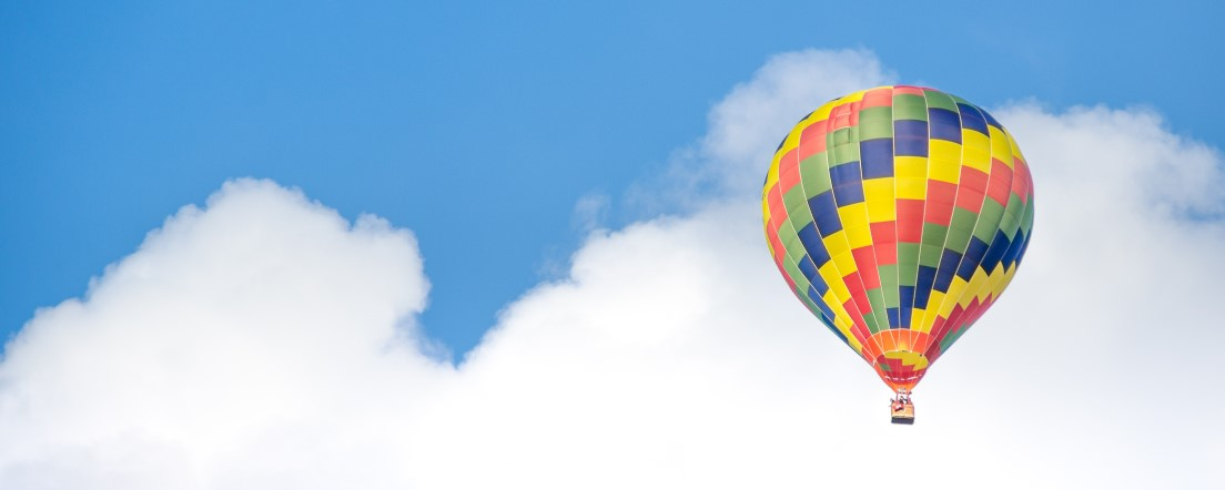 Hot air balloon in cloudy blue sky