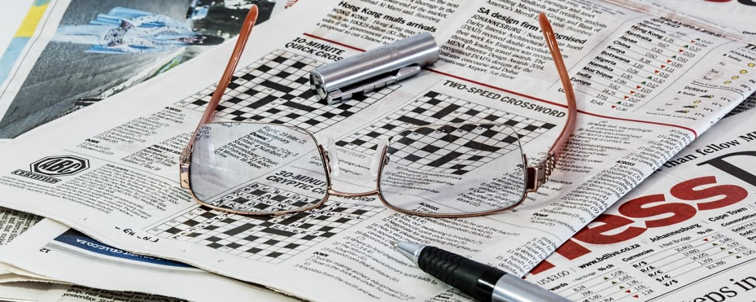 crossword in newspaper with glasses and pen
