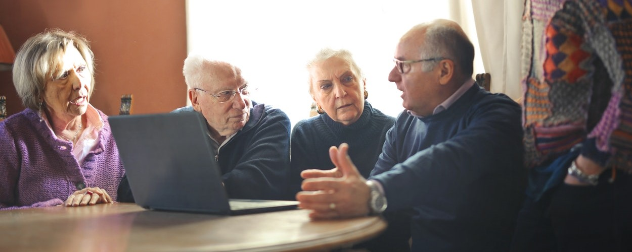 A group of four older people sitting around a table with a laptop.